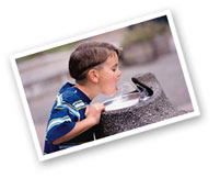 boy drinking out of a water fountain